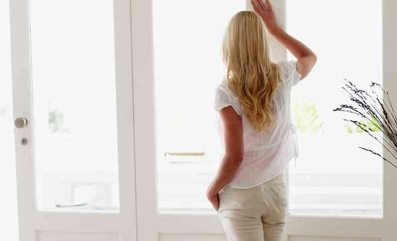 窓辺から外を眺める女性